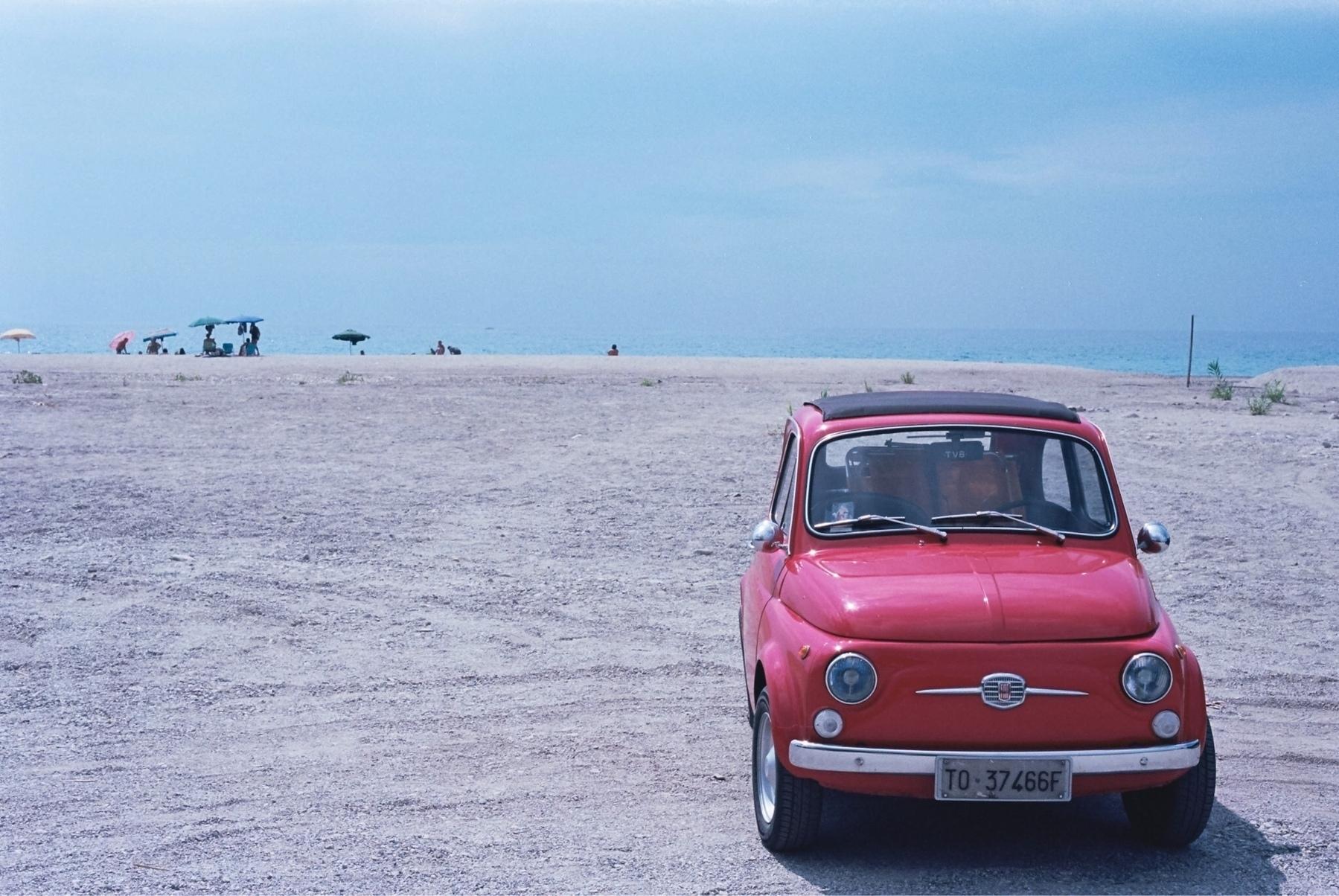 A classic Fiat sitting on an Italian beach.